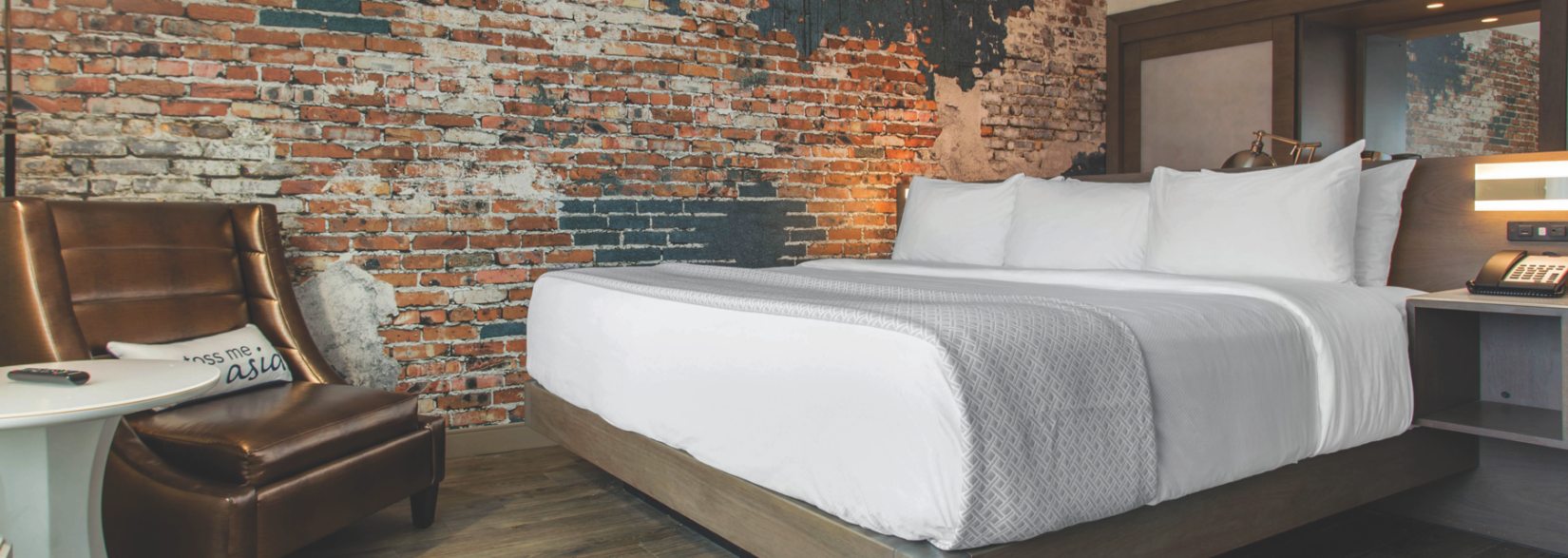 Hotel Bed with Exposed-Brick Wall