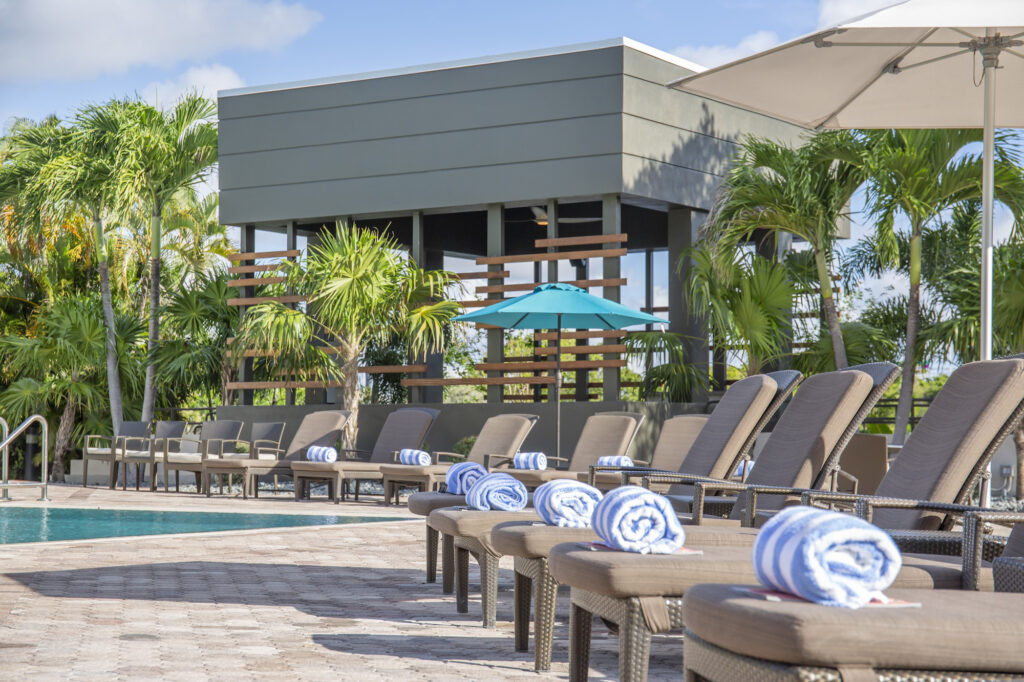 Hotel pool deck with folded towels on each lounge chair