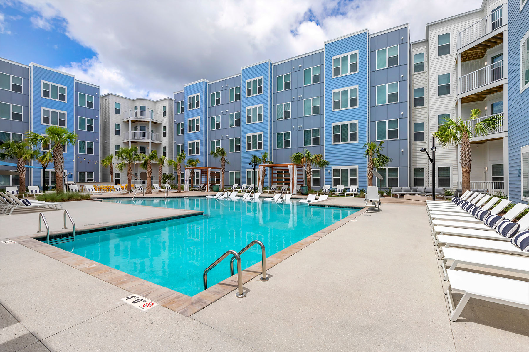 Apartment Community Pool with White Lounge Chairs