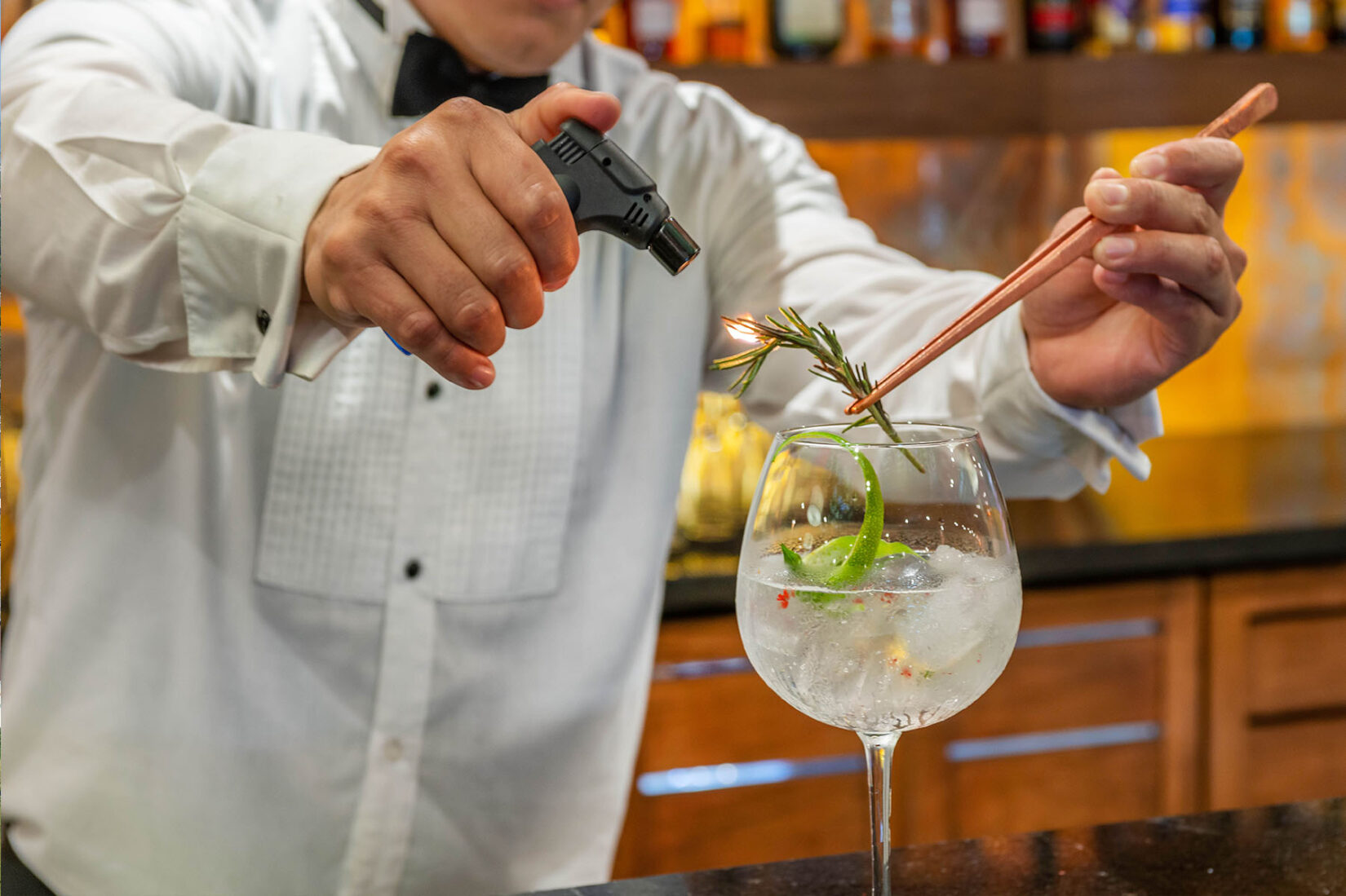 Omni Bar Bartender Lighting Rosemary on Fire to Make Drink