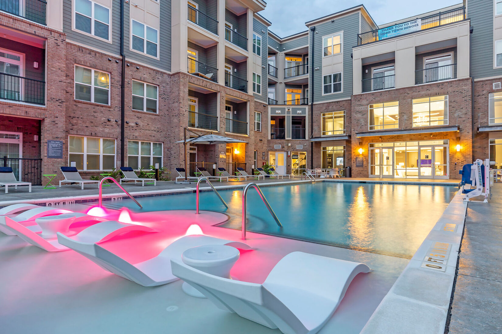 Apartment Community Pool with Pink Lights and Modern Lounge Chairs